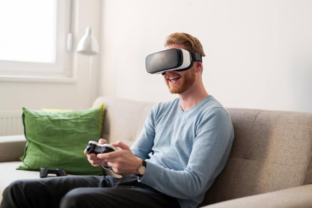 Mand spiller PlayStation i stuen